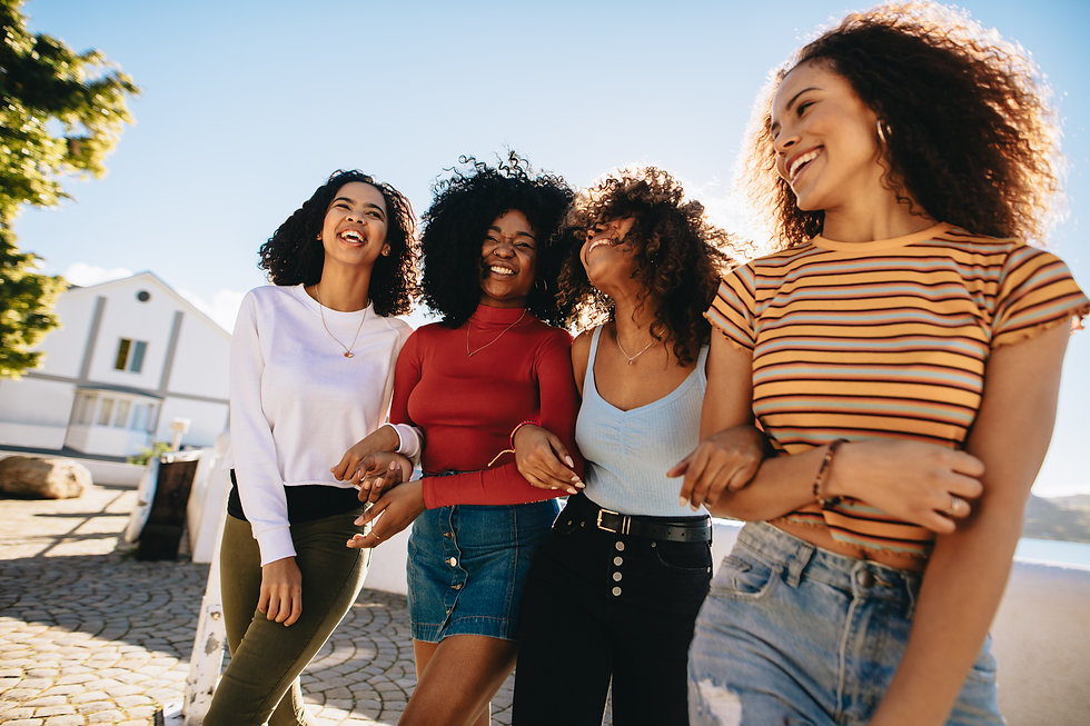 Mixed raced group of female friends walking together outdoors. Young women having fun outd