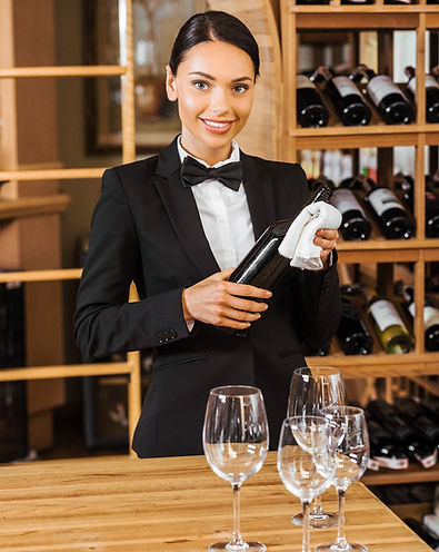 smiling female wine steward holding bott