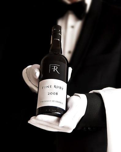 Waiter in tuxedo holding a bottle of red
