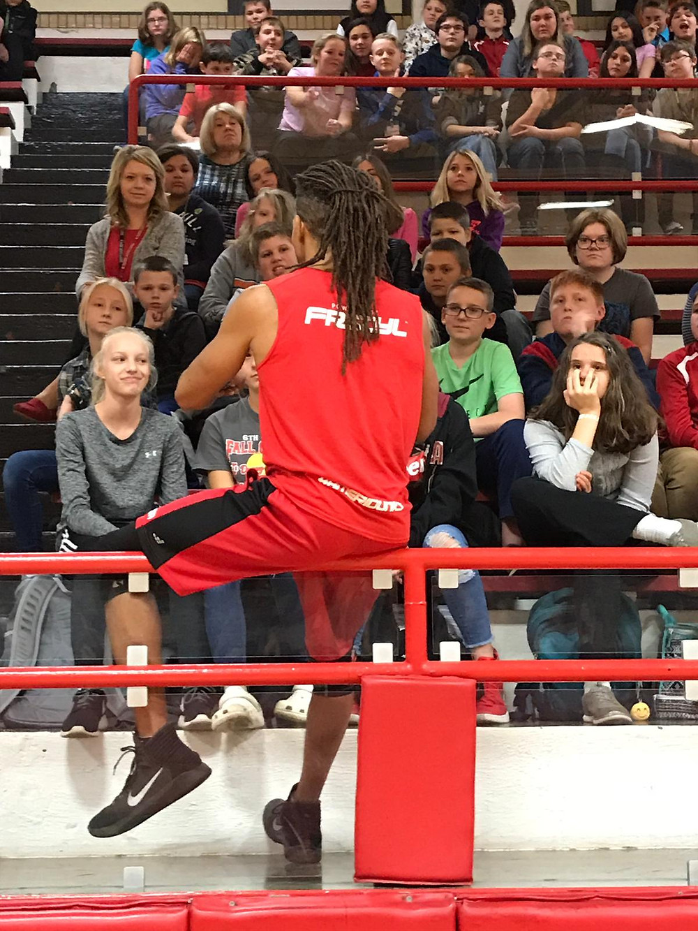 JLB in red speaking to Jr. High students in bleachers