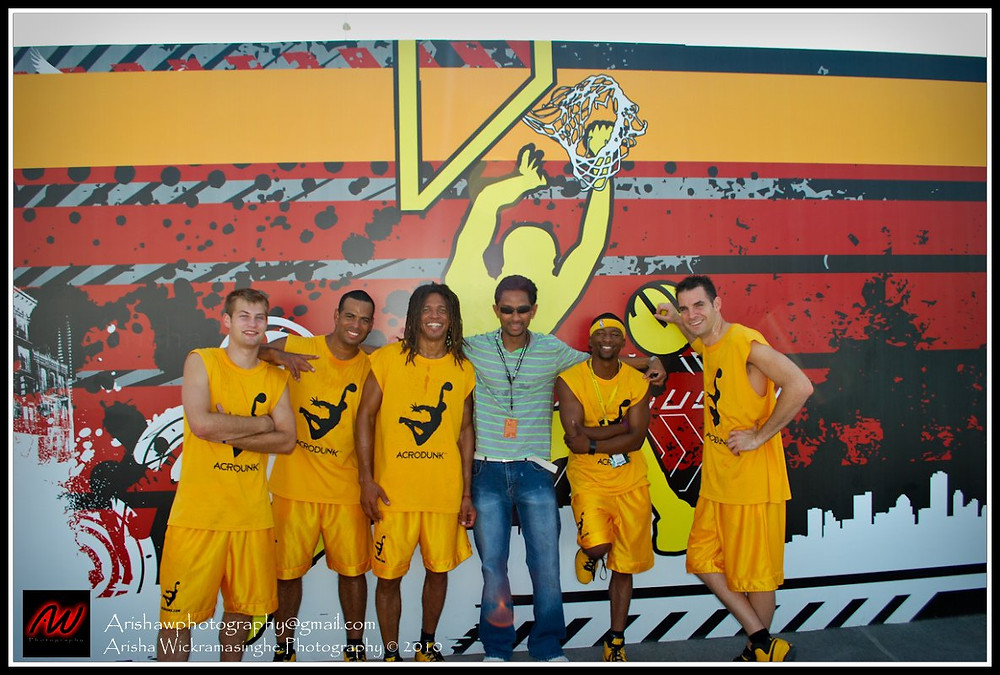 5 members of ACRODUNK in yellow gear with black ACRODUNK logos  standing in front of a mural with a basketball player dunking a ball