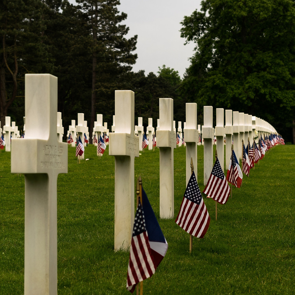 White crosses on graves in graveyard with American flags