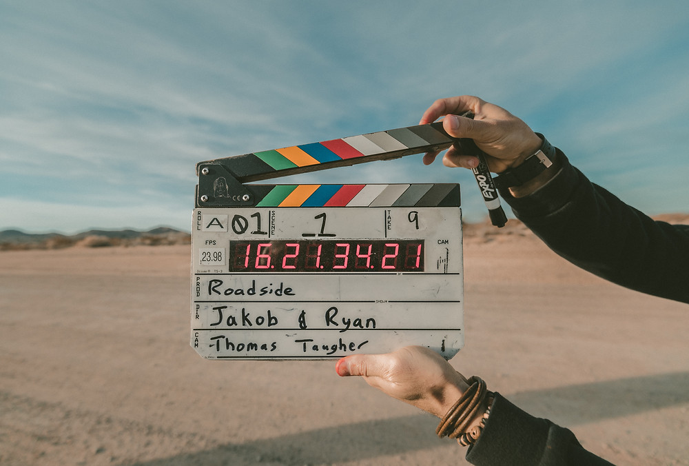 clapperboard held by two hands with desert in background