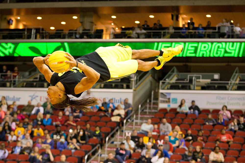 Jerry L. Burrell flipping and twisting with yellow basketball in hands