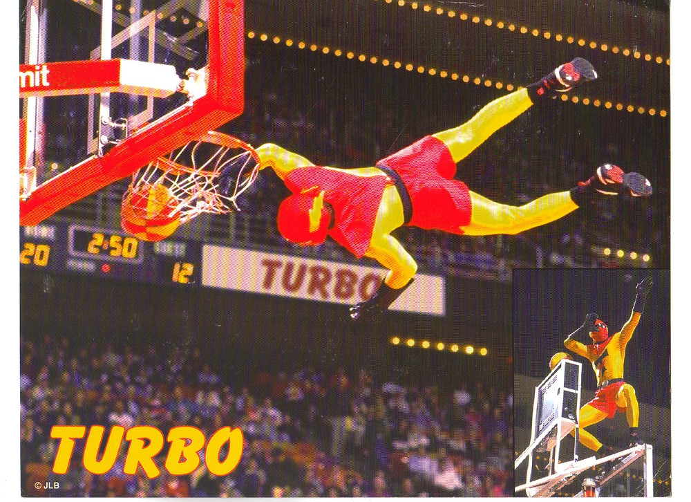 sports super hero dressed in red & yellow costume dunking basketball from a laid out prone position with TURBO text in left bottom corner