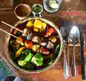 """""""Bowl of Goodness"""" sur base de riz rouge sauvage, brocolis, courges et poivrons rôtis, brochettes halloumi-tomates cerises et aubergines grillées., couvert en inox sur table en bois"""