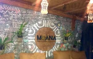 Décoration tahitienne et mur du restaurant Moana, tableau avec des écritures à la craie, plantes suspendues et coussins marrons