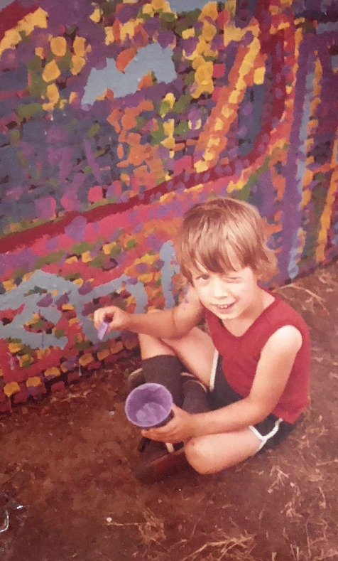 Boy poses while painting with Thomas