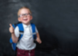 Happy smiling boy in glasses with thumb