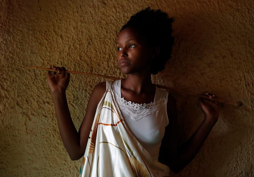 Diane Uwera (18), one of the few Rwandan women cow poets poses in her house in Bugesera, Rwanda.