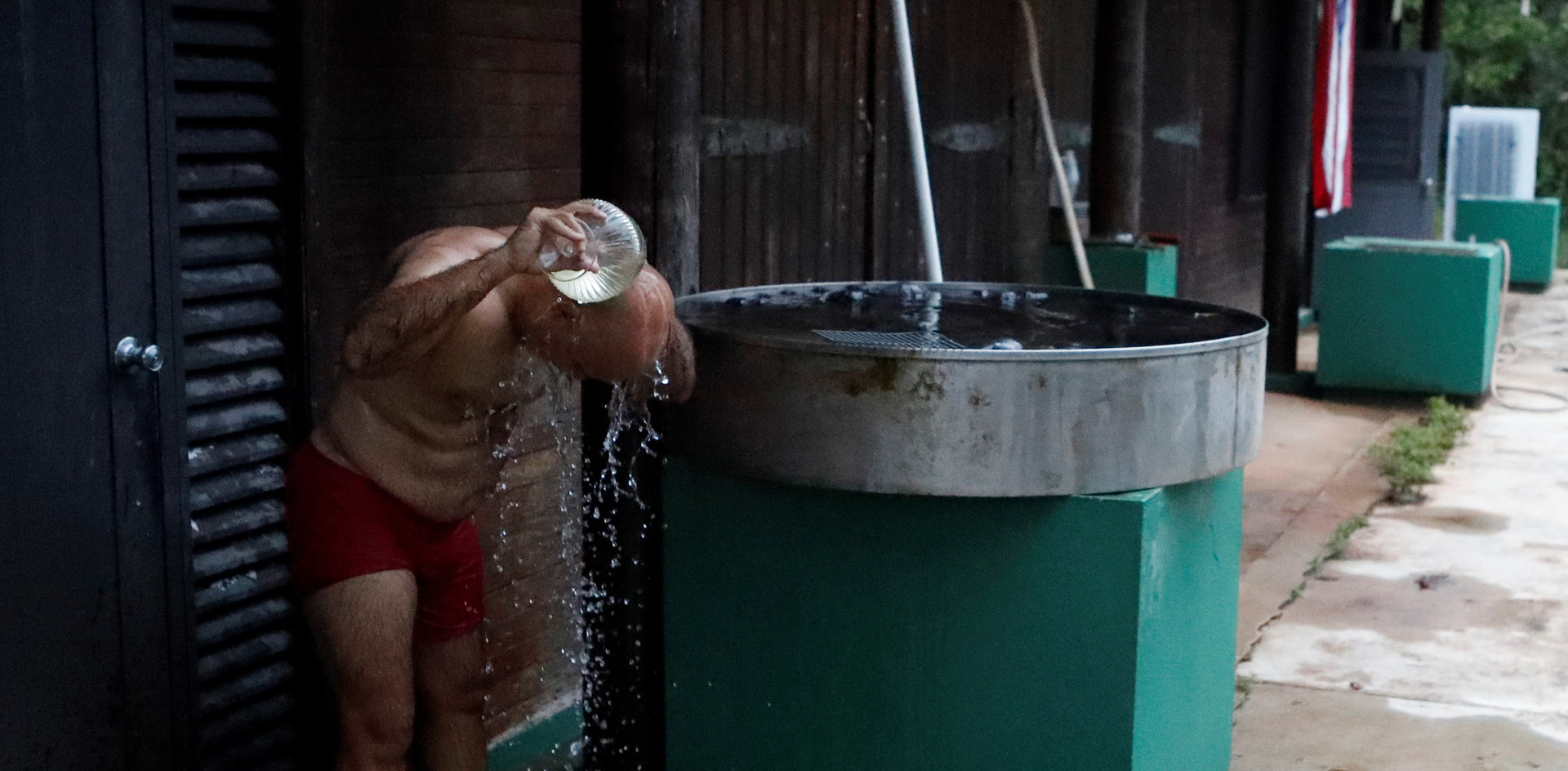 Ricardo Valentin, 62, bathes outside using collected rainwater at the Rio Abajo Aviary in Aricebo, Puerto Rico.