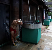 "Ricardo Valentin, 62, bathes outside using collected rainwater at the Rio Abajo Aviary in Aricebo, Puerto Rico on Tuesday, May 22, 2018. After Hurricane Maria hit the island in September 2017 much of the infrastructure was destroyed including the water pipes leading to the aviary. Without a steady supply of water, the aviary must rely on a water delivery truck, which comes on a weekly basis. ""The aviary sustained significant damage,"" said Valentin, ""not enough damage to render it not functional but enough to make the work difficult but not impossible."" Valentin works and lives at the aviary on weekdays. He bathes daily after jogging in the forest. In order to save water, he uses rainwater instead of the regular water supply."