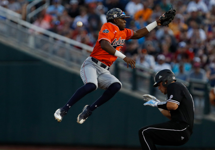 Auburn Tigers' second baseman Ryan Bliss (9) misses the throw against Mississippi State Bulldogs' catcher Dustin Skelton (8) in the sixth inning in the 2019 College World Series at TD Ameritrade Park in Omaha, Nebraska.