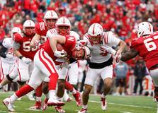 "Bo Kitrell (red, center) charges with the ball into Avery Anderson (white, right) and Breon Dixon (white, left) during a play at the Huskers' annual Spring Game in Memorial Stadium on Saturday, Apr. 21, 2018 in Lincoln, Neb. The Husker Spring Game is held as a glorified practice for its players in a Red versus White setup. The game ended with the Red team winning 49-9. This year the game was attended by a record breaking crowd of 86,818 people. Excitement has been built up with the arrival of the Huskers' new coach, Scott Frost, a Husker alumni quarterback. ""I think the guys have come a long way already,"" said Frost, ""I told them that they can't see this as the end of the process."""