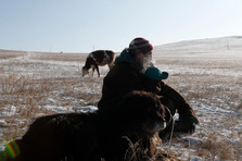 "Tsogbayar Khorol, 49 watches his livestock with his herding dog, Arslan, 16, by his side in the Bornuur province on New Years Day, 2019. Khorol lives about two hours outside of Ulaanbaatar, the capital of Mongolia. He owns around 300 heads of livestock, which consists of cows, sheep and goats. He makes money off of selling their milk to the nearby town of Bornuur. Arslan is a Bankhar dog, which are a Mongolian landrace used as herding dogs dating back to the time of Genghis Khan. ""I traded Arslan for 40 male goats,"" said Tsogbayar. ""Before I had Bankhars, wolves would come into the fence and take the livestock. After getting Bankhars, we haven't lost any animals to the wild beasts."""