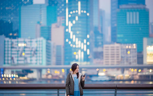6161 Woman using smartphone by the harbo