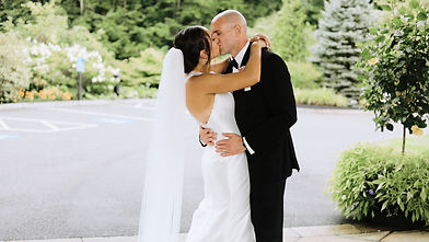 Couple on their wedding day kissing in front of venue