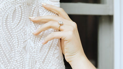 Bride wearing engagement ring playing with her wedding dress