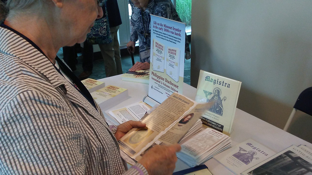 """Conference attendee reads a pamphlet about """"Magistra"""", a journal of women's spirituality in history, whose editorial board includes Sister Laura Swan, OSB, Esther de Waal, Sister Hugh Feiss, OSB, and Sister Mary Forman, OSB."""