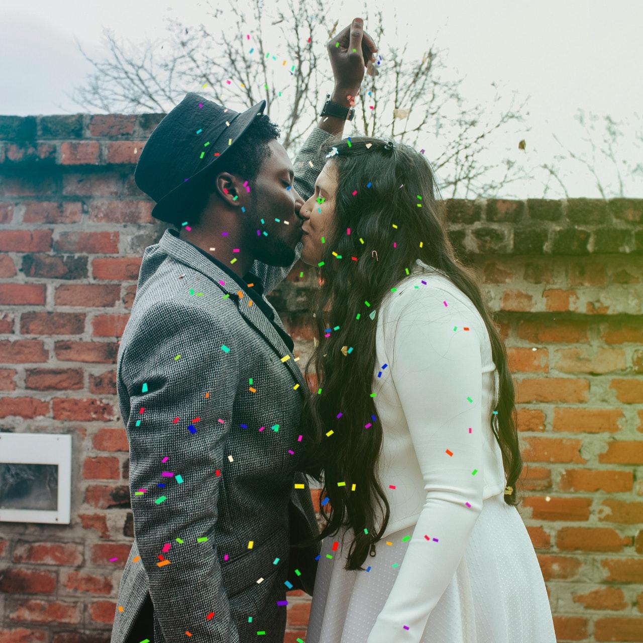 man-in-hat-kissing-woman-in-white-dress-
