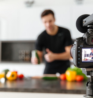 close-up-of-video-camera-filming-young-smiling-male-blogger.jpg