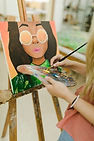 close-up-woman-s-hand-painting-easel-wit