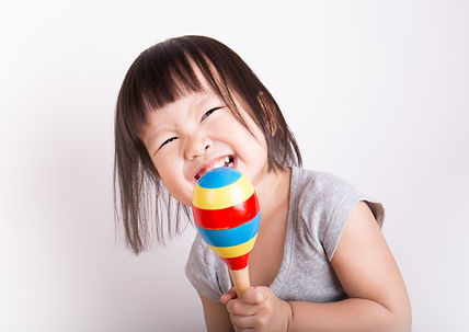 Little asian child play the maracas gray