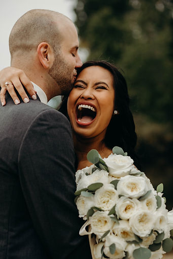 Bride Laughing while groom is kissing he