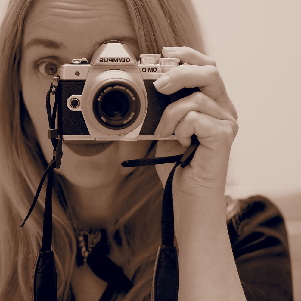 Girl taking self portrait in mirror in Sepia with Olympus E-M10 Mark III
