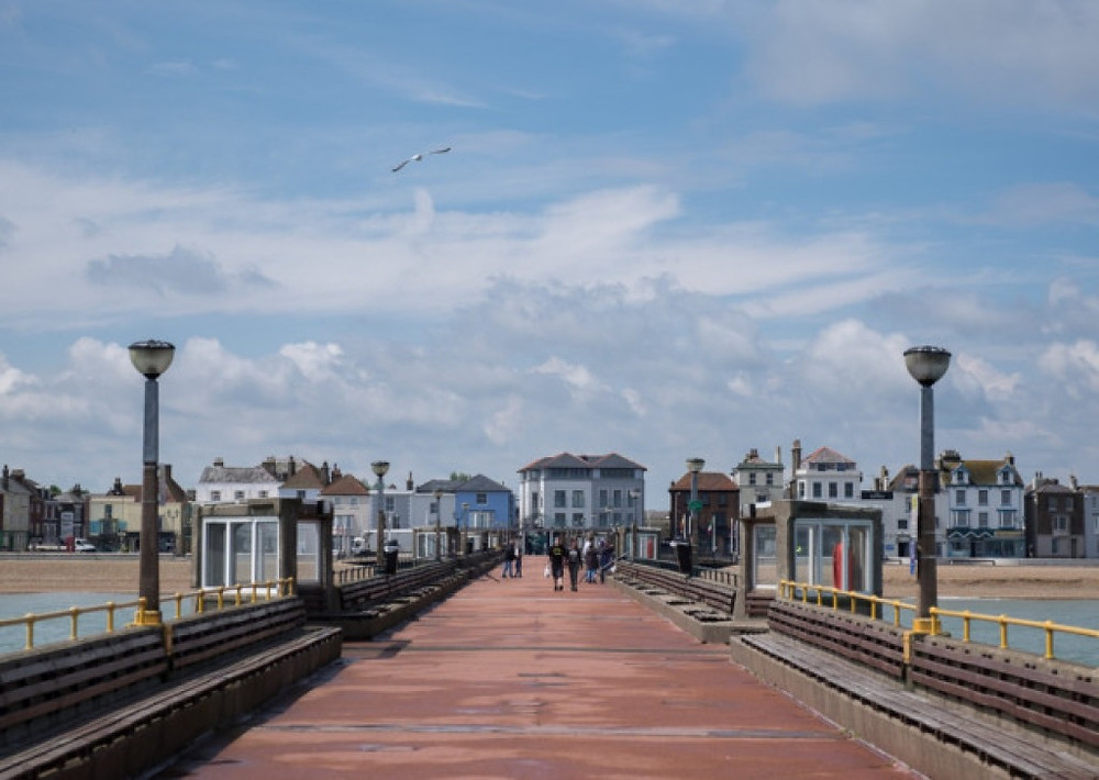 People taking a walk along Deal Pier, Pastel Buildings, Seagull flying across the blue sky .