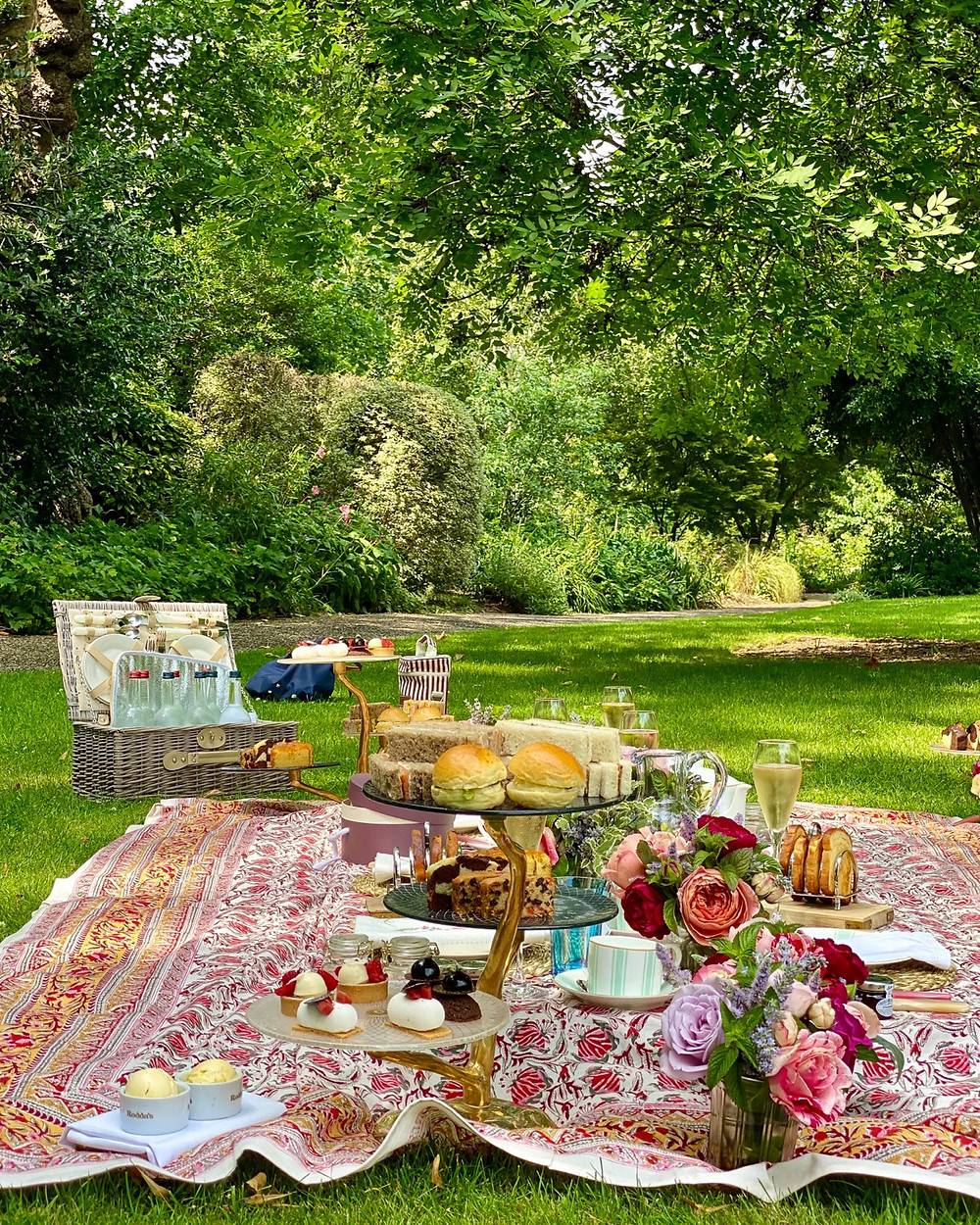 English Afternoon Tea Picnic in gardens with picnic basket , cream tea , scones , English Roses and pretty tablecloth .