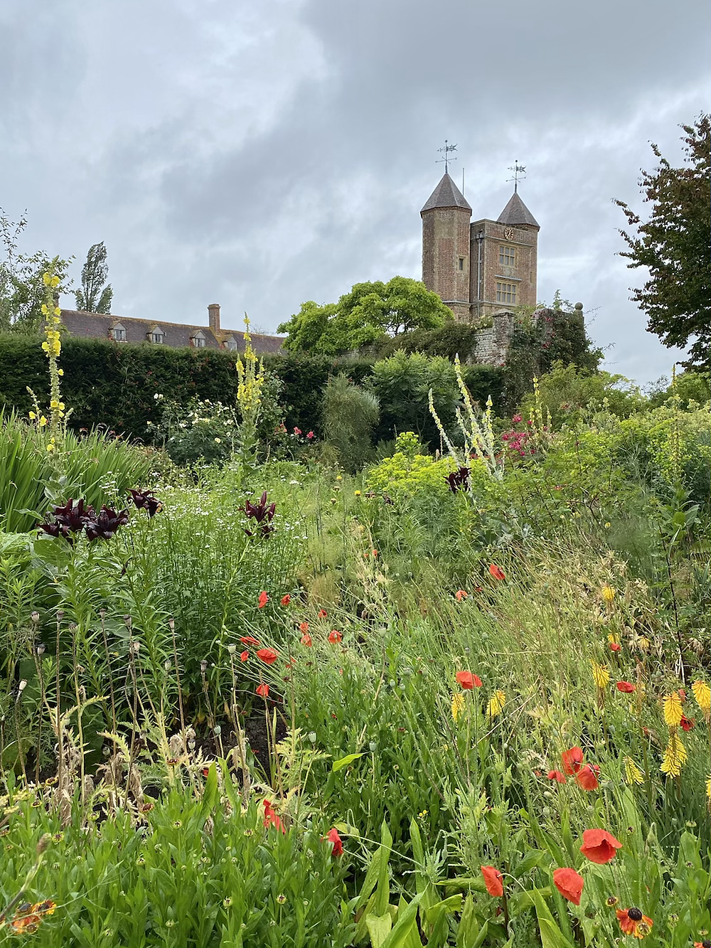 Sissinghurst Castle Garden in Kent Tower with Summer poppies . National Trust South East Kent .