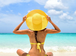 Happy carefree woman relaxing sitting in sand enjoying tropical beach destination. Perfect