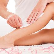 Waxing Behandlung an einem weiblichen Bein.