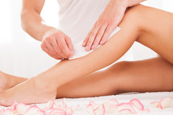 Beautician Waxing A Womans Leg