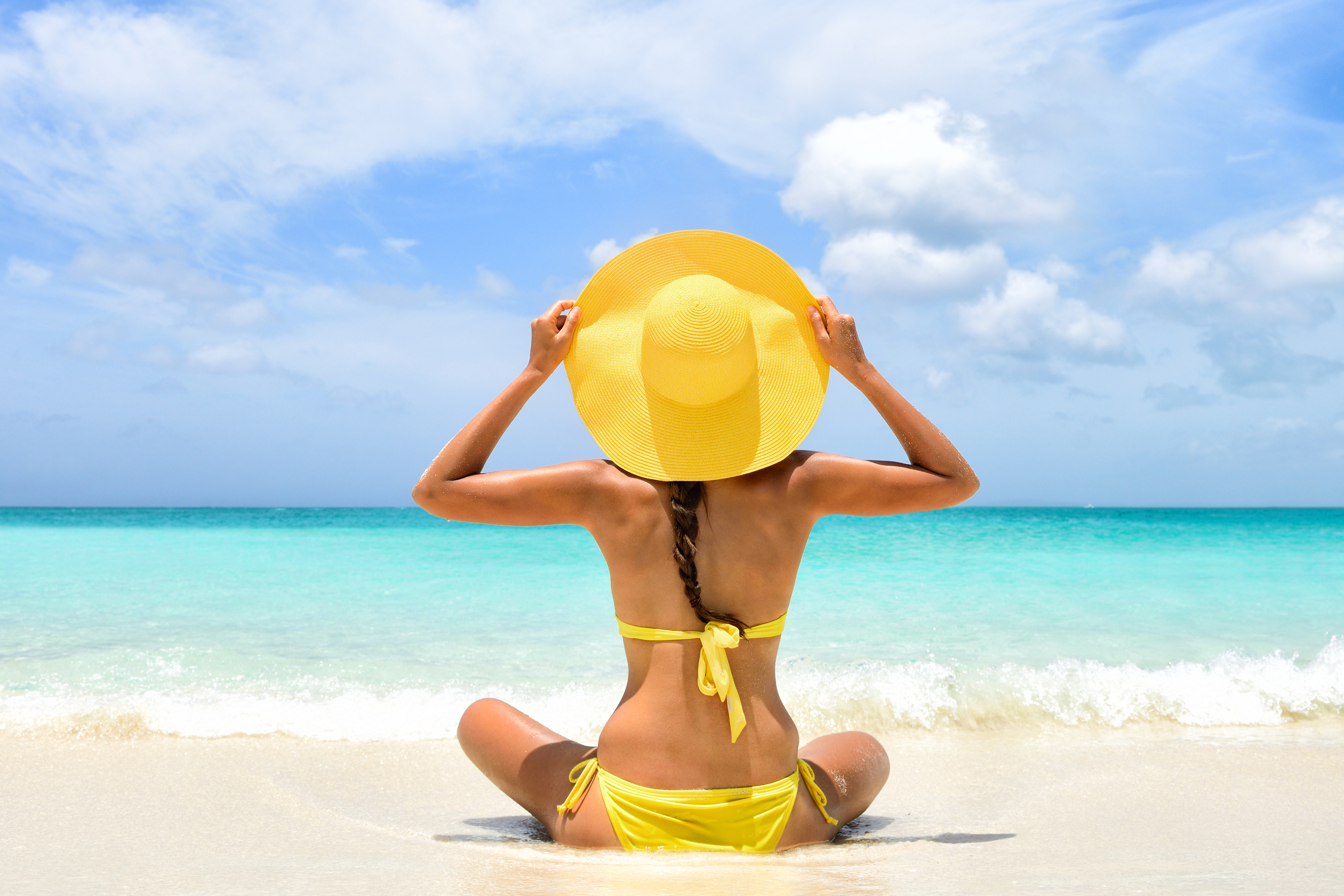 Happy carefree woman relaxing sitting in sand enjoying tropical beach destination. Perfect paradise