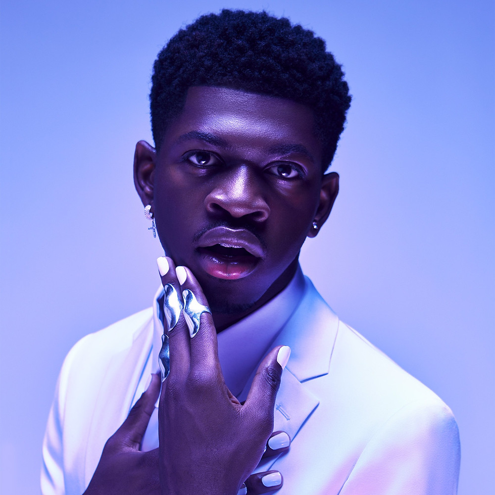 Lil Nas X in a suit hand touching his face with white painted nails. Blue and purple background.