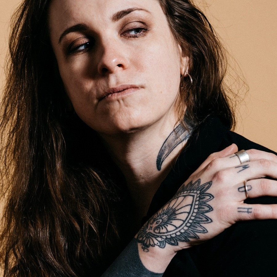 Laura Jane Grace looking to the side with her hand on her shoulder orange background.