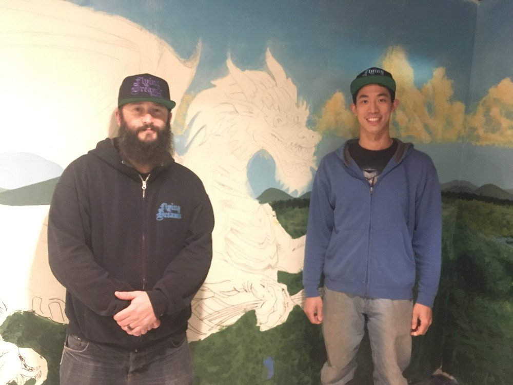 Flying Dreams owner Dave Richardson (left) and Head Brewer Lee Chiang (right) stand in front of a mural painted by artist Kai Griffiths.