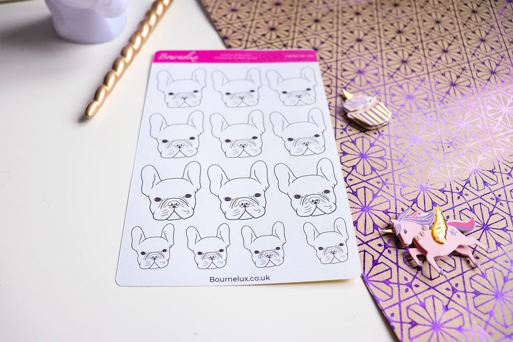 A sticker sheet of colour your own French Bulldogs, placed on a white and patterned background, surrounded by a cupcake and unicorn decorations