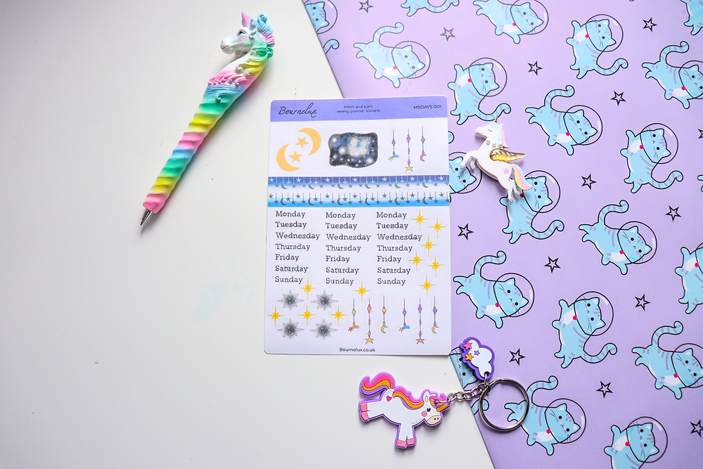 A sticker sheet containing stars, galaxies and days of the week stickers, placed on a white and patterned background with a pen and a keyring as decoration around it