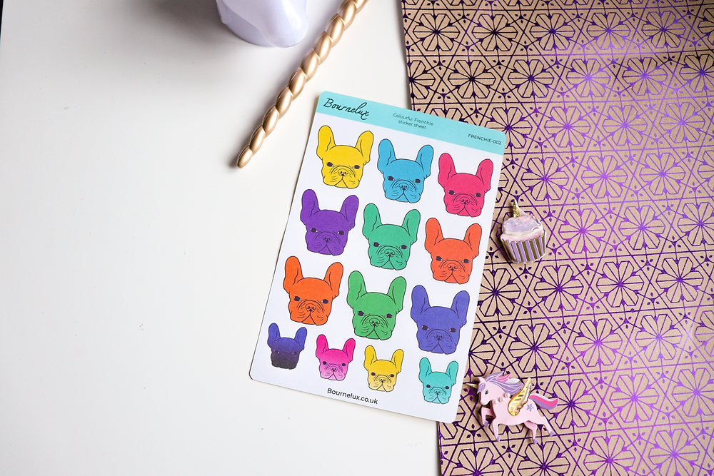 A sticker sheet of brightly coloured French Bulldogs, placed on a white and patterned background, surrounded by a cupcake and unicorn decorations