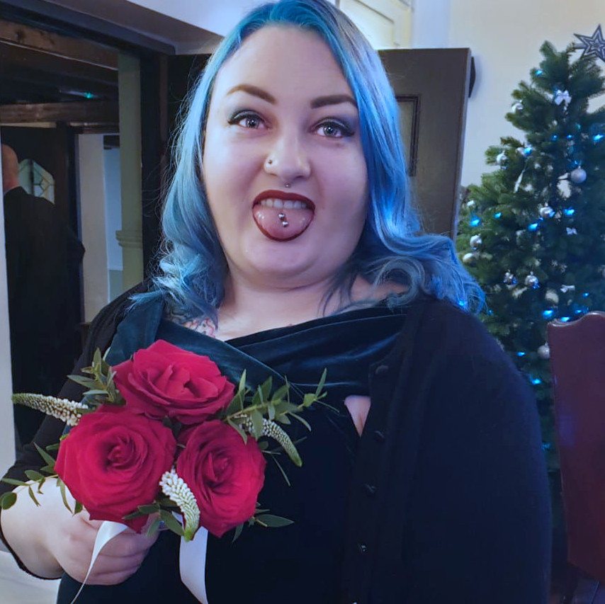 A blue haired lady holding a bouquet of flowers, with her tongue poking out, christmas tree in the background