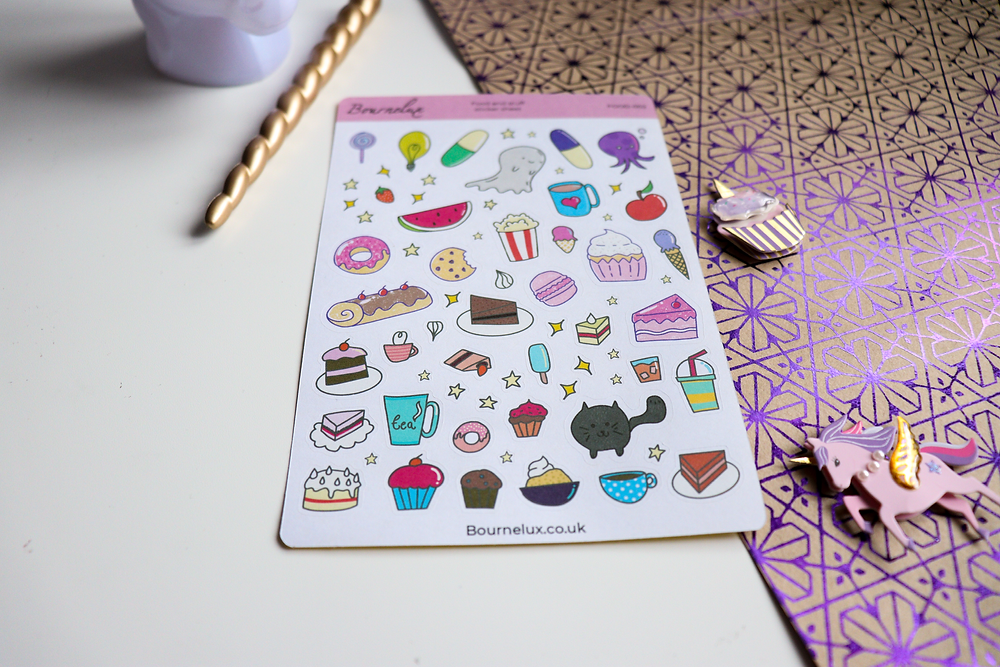 A sticker sheet full of yummy food and stuff, placed on a white and patterned background, surrounded with a cupcake and unicorn