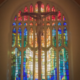 The holy cross and stained glass window