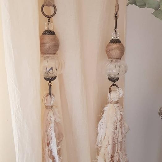 Correcortinas, esfera yute y vidrio con caída de penacho de tiras de tela