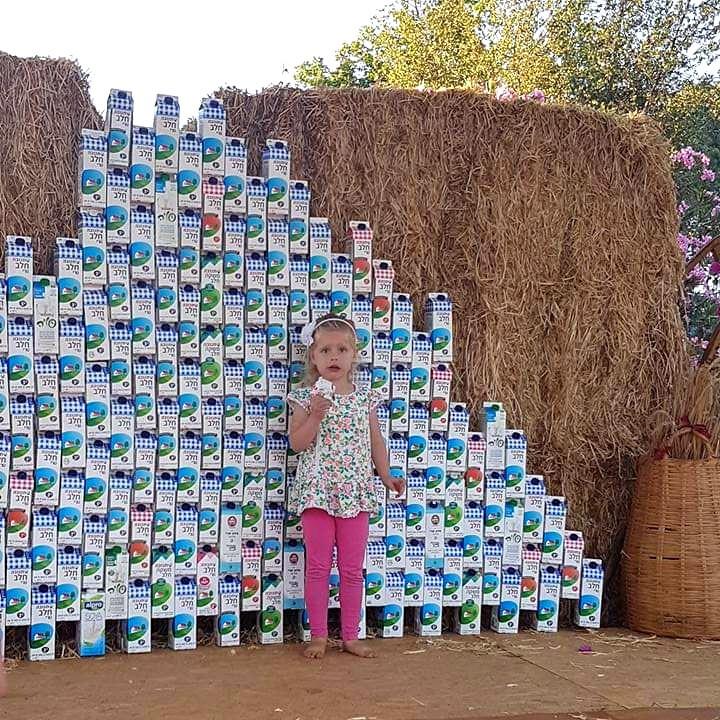 גל בטקס שבועות בקיבוץ עם קיר של חלב