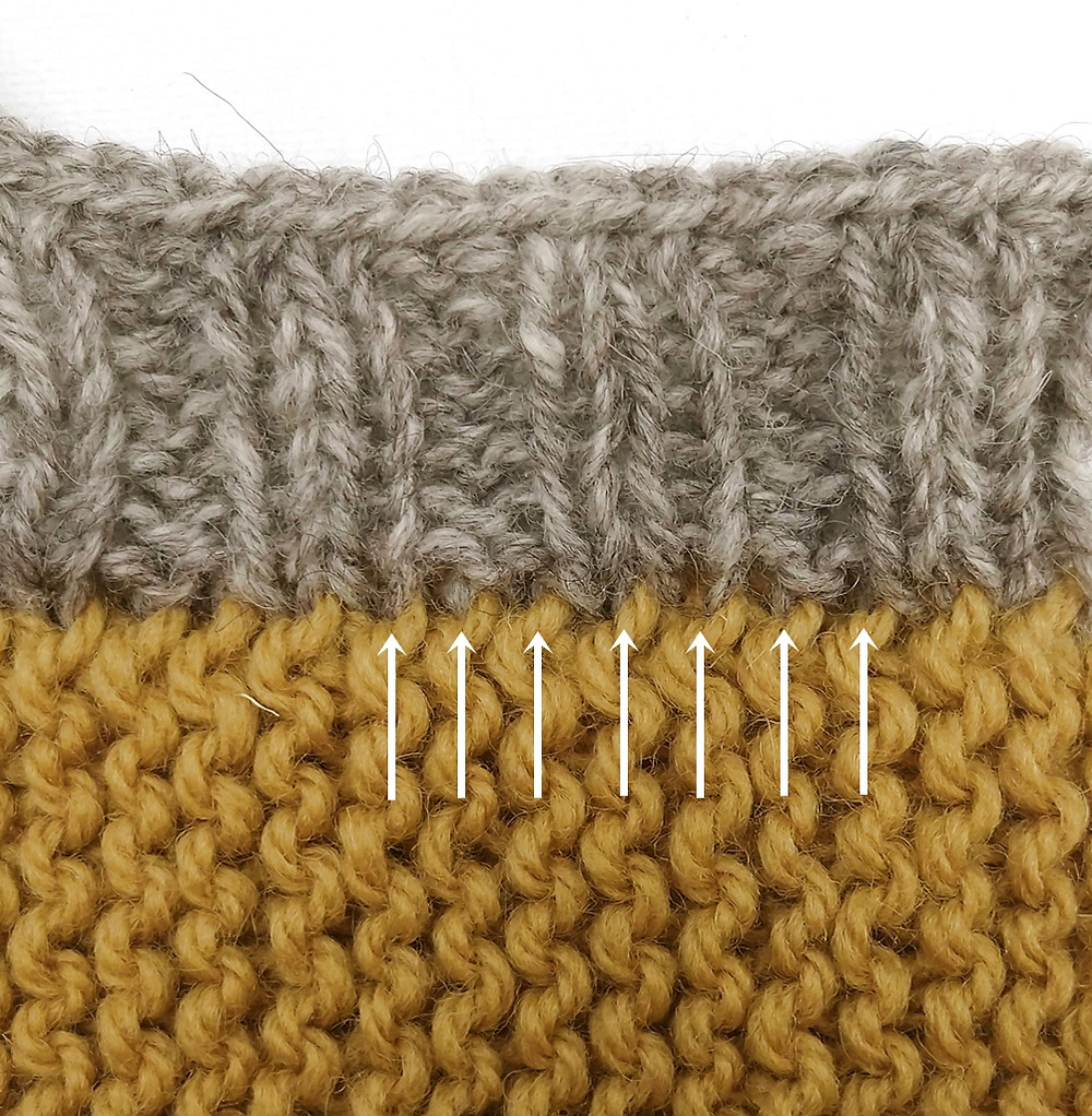 Typical pick-up ratio in garter stitch is 1:2, that is, 1 stitch for every garter ridge.