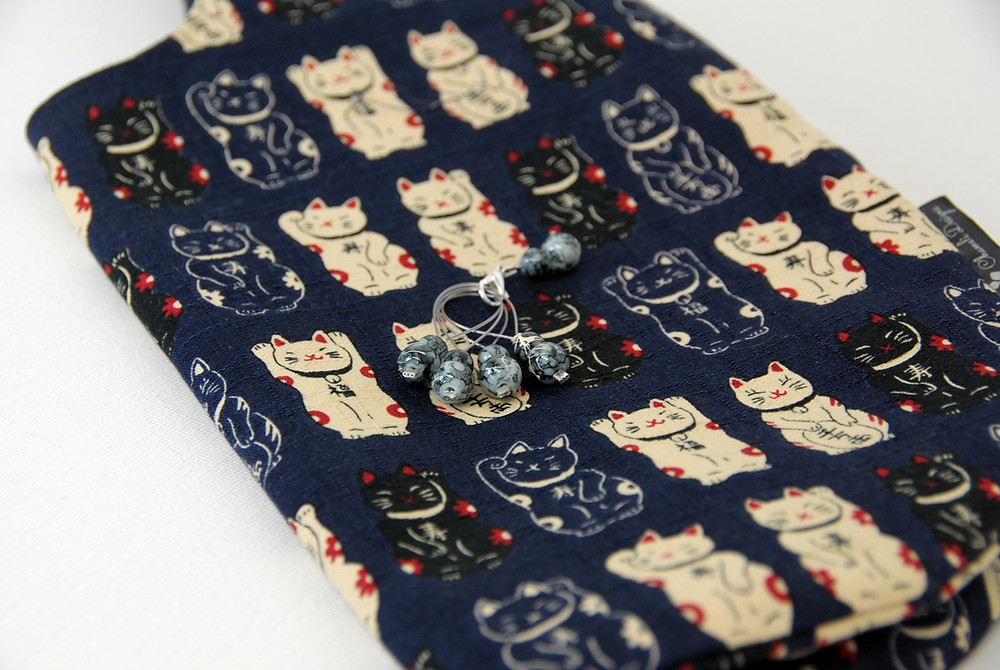 Japanese knot bag with waving cats and black-and-white stitch markers