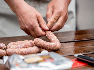 Butcher making sausages in meat factory.